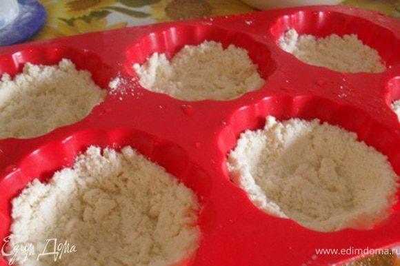 Формочки для маффинов смазать маслом, уложить слой крошки, сделать бортики.