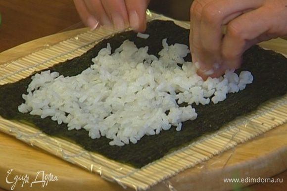Застелить коврик для суши пищевой пленкой, положить сверху лист нори и выложить на него слой суши-риса толщиной примерно 9 мм.
