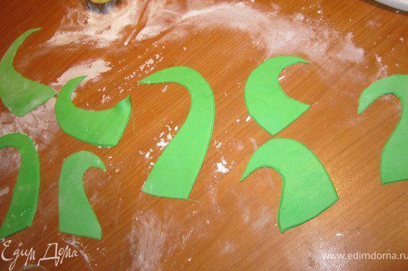 Раскатать зеленую мастику и вырезать, произвольно, завитушки.