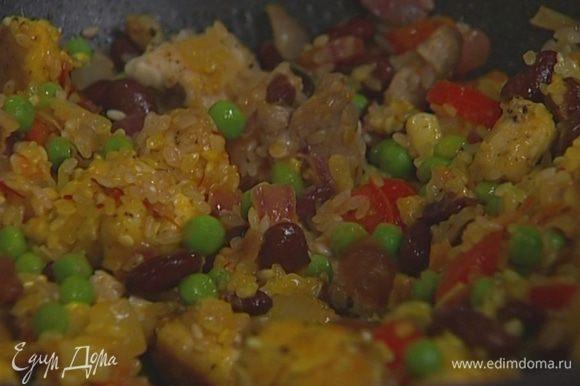 Добавить в сковороду отваренную фасоль, размороженный горошек, нарезанные колбаски, свинину, курицу, рис и размоченный шафран, влить 50 мл вина и 1 ст. ложку оливкового масла.