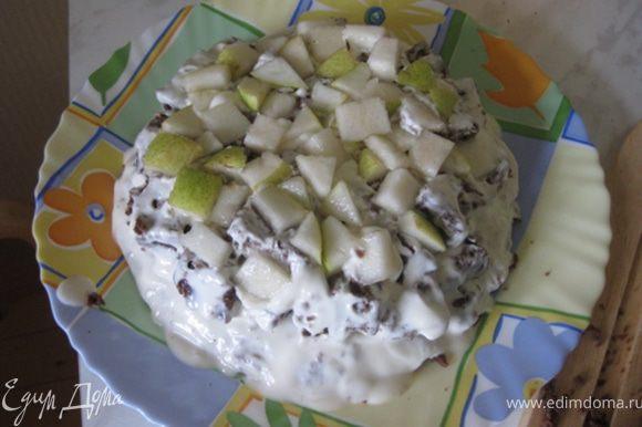 Выложите первый слой из кубиков бисквита, обмазанных в креме (от центра к краям). Затем слой из ананаса и орехов.
