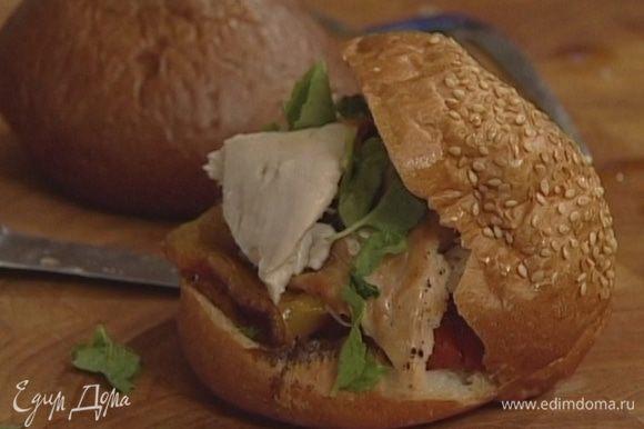 Уложить внутрь каждой булочки половину желтого перца, один помидор, кусочек запеченной курицы и несколько листьев петрушки.