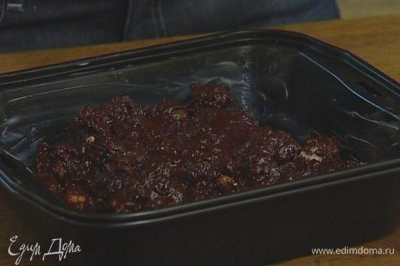Добавить изюм, оставшееся печенье, выложить все в форму и слегка утрамбовать. Затянуть пищевой пленкой и поставить на 2 часа в холодильник.