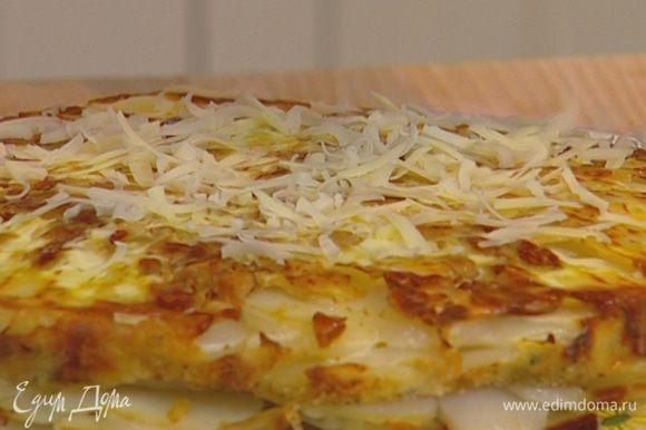 Готовый пирог вынуть из формы, перевернув так, чтобы миндаль оказался сверху, и присыпать остатками натертого сыра.