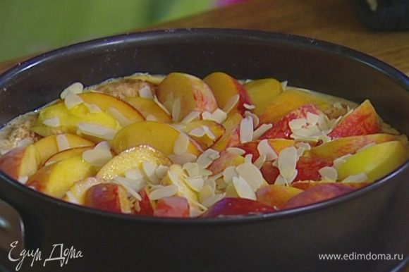 Остывший корж присыпать половиной миндальной крошки, выложить крем, присыпать оставшейся крошкой. Уложить на крем как можно больше персиков.