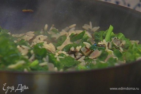 Снять рис с огня, добавить листья базилика, пармезан и все перемешать.