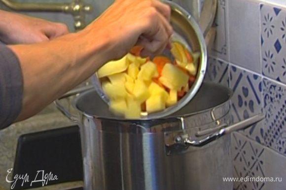 Всыпать горох, минут через 10–15 добавить картофель и морковь. Посолить, поперчить и варить суп до готовности, 20–25 минут.