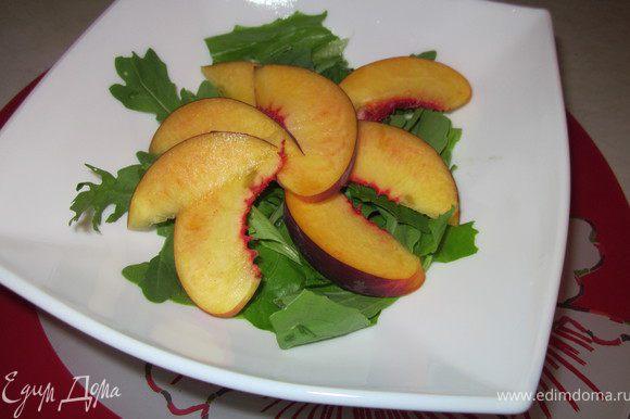 Нарезать персики крупными кусочками и разбросать на листья