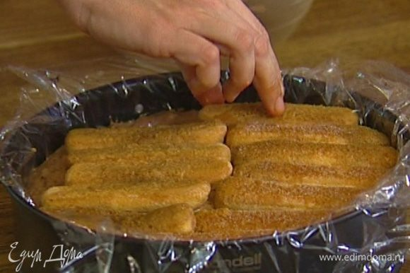 Круглую форму для выпечки выстелить пищевой пленкой. На дно формы уложить слой печенья, затем крем, сверху снова слой печенья. Затянуть сверху пленкой и поставить в морозилку минимум на 4 часа.
