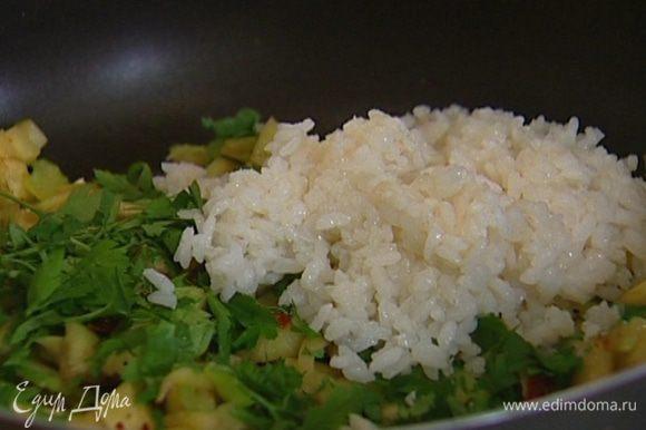Посолить, поперчить, добавить петрушку, отваренный рис, прогреть все вместе и снять с огня.