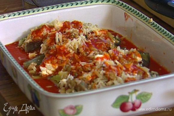 В глубокую керамическую форму вылить половину томатного соуса, уложить начиненные баклажаны, присыпать оставшимся пармезаном и полить оставшимся томатным соусом.