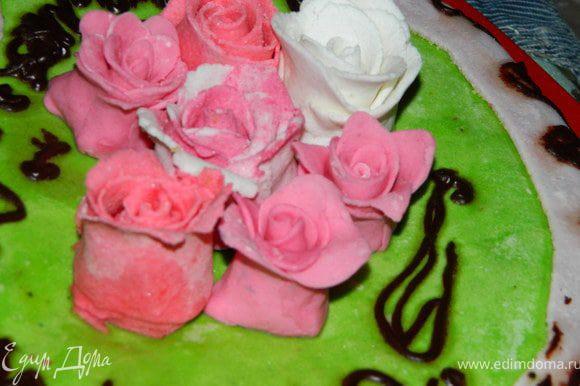 Я раскрашивала мастику в розовый, алый, зелёный, сереневый цвета. Зелёную раскатала и уложила сверху, полуился газон.Сиреневой обкрутила бока, а из остальной накретила роз.