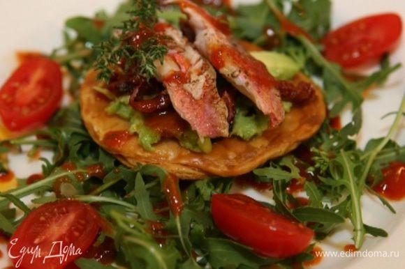 Выложить руколу и помидоры черри на тарелки, полить заправкой, сверху положить кружок теста с рыбой.