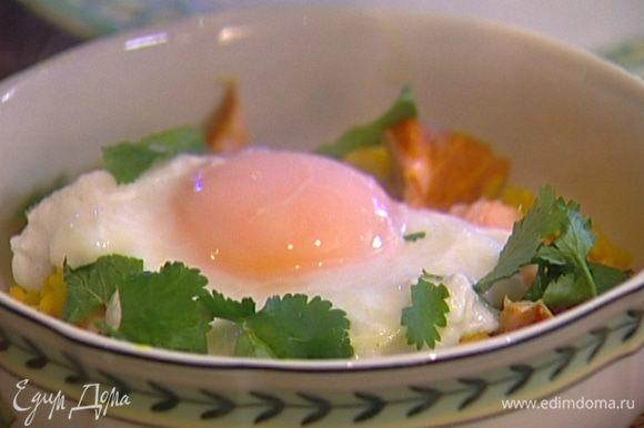 Выложить в глубокую тарелку рис басмати, сверху семгу и яйцо пашот, присыпать листьями мяты и кинзы.
