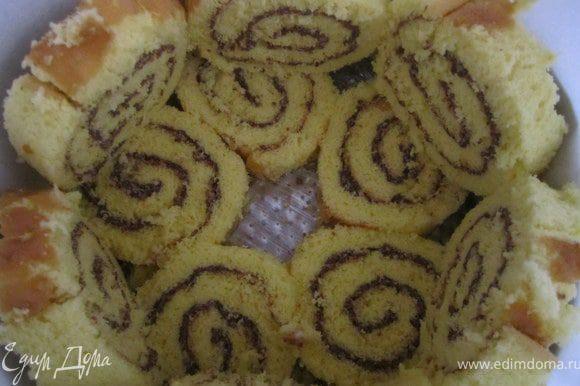 Дно разъемной формы покрыть пищевой пленкой, бока пергаментной бумагой. Выложить кусочки рулета.
