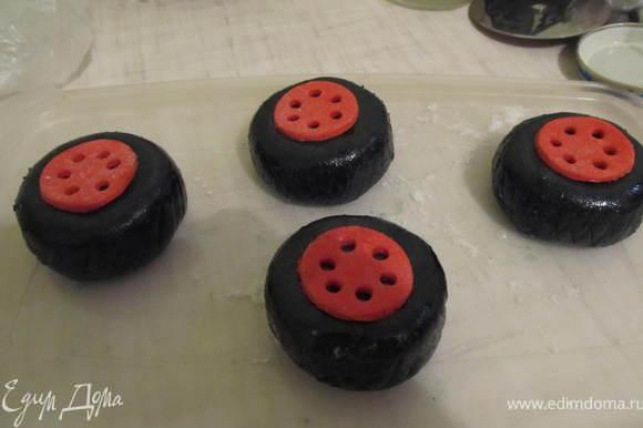 Из красной мастики вырезать маленькие кружочки, в каждом с помощью коктельной трубочки вырезать дырочки,и приклеить с помощью водки в центр каждого колеса. На колесах зубочисткой нанести рисунок шин.