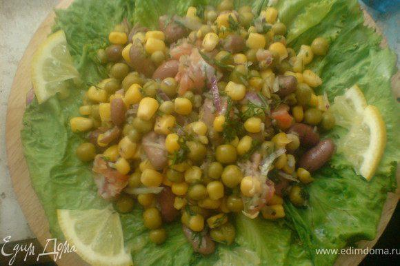 заправить оливковым маслом с добавлением лимонного сока,выложить на листья салата и украсить лимоном