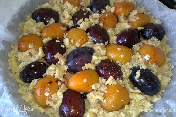Смешать крупу, муку, сахар, масло, орехи, цедру лимона. Форму застелить бумагой для выпечки, выложить в форму 3/4 теста, затем сверху выложить сливы и абрикосы. Поверх ягод (кабы между ними) равномерно распределить остатки теста.