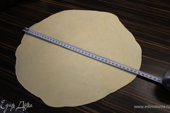 Достать тесто из холодильника. Раскатать его в диаметре около 38 см, присыпав стол и тесто небольшим количеством муки. На противень положить пергаментную бумагу, присыпать чуть мукой и переложить тесто с помощью скалки - На самом деле, тесто настолько комфортное, что это делается очень легко и приятно:)