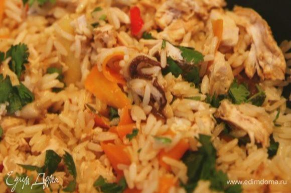 Когда рис будет готов, добавить курицу и 2/3 нарубленной кинзы, влить соевый соус, перемешать и посыпать оставшейся кинзой.