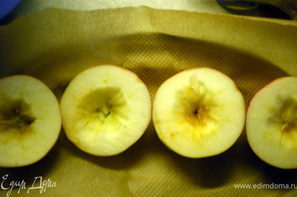 Выложить яблоки на противень, застеленный бумагой.