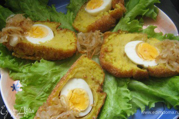 Картофель очистить и сварить в под солёной воде, слить воду, обсушить и размять в пюре. Добавить в пюре сливочное масло, 1 взбитое яйцо, муку, пряности, приправить солью и перцем по вкусу, тщательно перемешать. Вареные яйца плотно облепить со всех сторон картофельным тестом, обмакнуть во взбитое яйцо, а затем обвалять в панировочных сухарях. Растительное масло разогреть в казане.Выложить яйца в разогретое масло. Жарить, пока корочка не станет золотисто-коричневой. Очень острым ножом разрезать яйца пополам и подавать с жареным луком или томатным соусом.