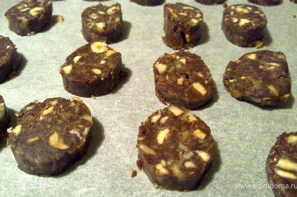 Колбаски вынуть из холодильника и дать им немного полежать (минут 5-7). Иначе я начала резать и они начали крошиться. Колбаски нарезать кружочками толщиной не боле 1 см ( в оригинале 0,5 см) горячим ножом. И выложить на противень с пекарской бумагой.