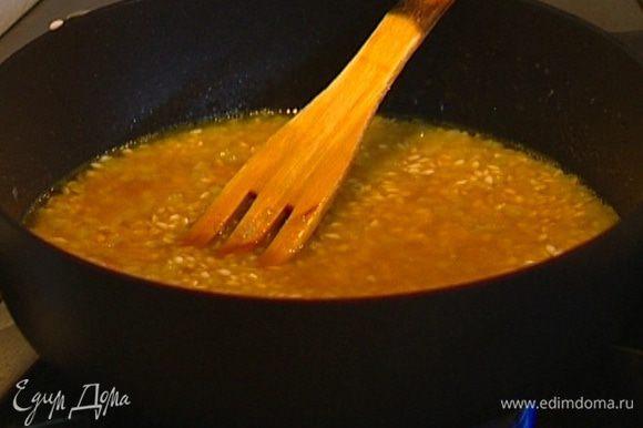 Влить 200 мл вина, так чтобы рис был им покрыт, и продолжать готовить, пока вино не выпарится.
