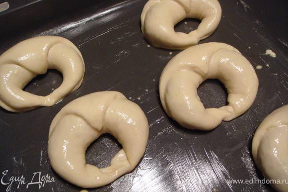 Выкладываем булочки на смазанный противень, накрываем смазанной маслом пищевой пленкой и ставим в теплое место на 30-40 минут. После расстойки смазываем булочки смесью желтка и 1 ст.ложки молока. Ставим в духовку, разогретую до 200°С на 15 минут по подрумянивания.