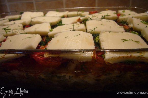 Достаём форму из духовки, сбрызгиваем пряным соусом, посыпаем укропом и накрываем пластиками моцареллы.