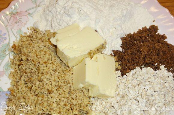 Орехи измельчите в блендере. Масло желательно предварительно подержать в морозильной камере и порезать кусочками. Из масла, сахара, муки, хлопьев и орехов приготовьте крошку.