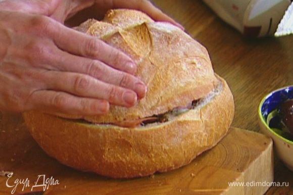 Положить внутрь нижней половины батона три куска колбасы, три куска салями, три куска сыра, затем снова по три ломтика салями и вареной колбасы; накрыть все верхней половиной хлеба и придавить так, чтобы «крышка» коснулась начинки.