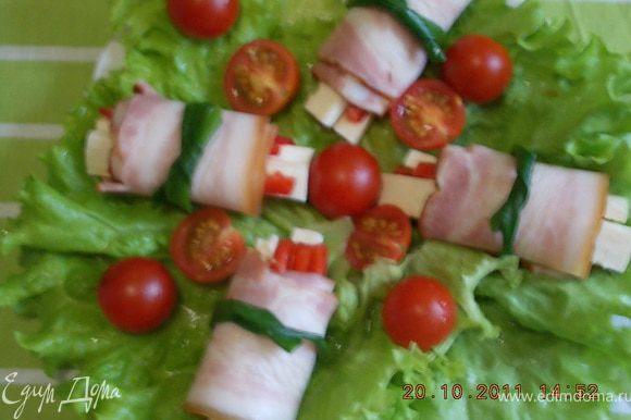 рулетики перевязать стрелочками зелёного лука,уложить на листья салата,украсить помидорами черри
