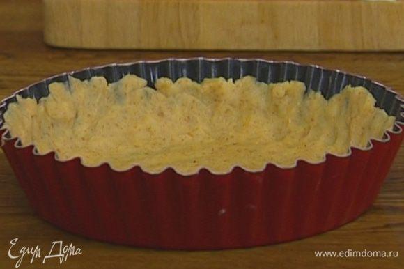 Рабочую поверхность присыпать мукой, раскатать тесто в пласт и переложить в форму для выпечки, равномерно распределив его по дну и бортикам.