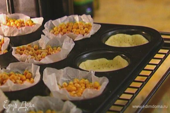 Отправить формы в разогретую духовку на 5 минут, затем удалить горох и выпекать еще 5 минут.