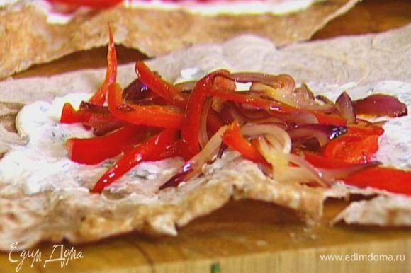 Половинки лаваша смазать сметанным соусом, выложить на каждую перец с луком и яйцо, свернуть в рулет.