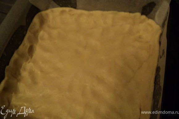 Дно и бока формы застилаем бумагой для выпечки, смазываем растительным маслом. Выкладываем раскачанное тесто и формируем небольшие бортики.
