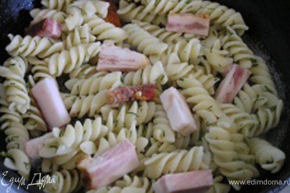 Разогреть сковородку с растительным маслом, выложить макароны и нарезанный кусочками бекон.