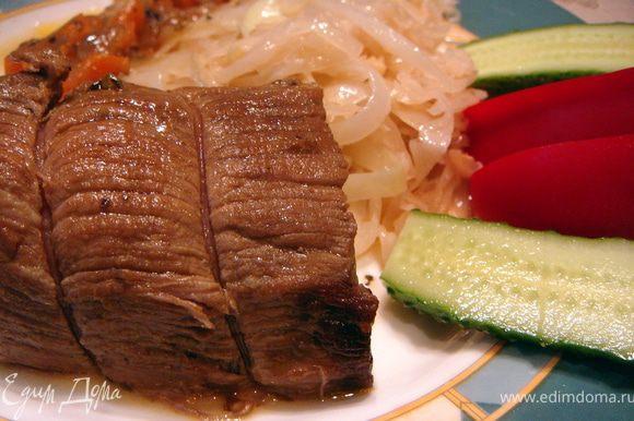 Достать куски мяса из соуса, срезать шпагат, нарезать на порционные кусочки и подавать на стол. На гарнир я подавала жареную на сливочном масле капусту. Не забыть полить мясо овощным соусом. Приятного аппетита.