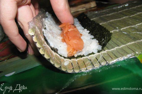 Аккуратно сворачиваем (придерживая начинку пальцами) до той части, где заканчивается рис.