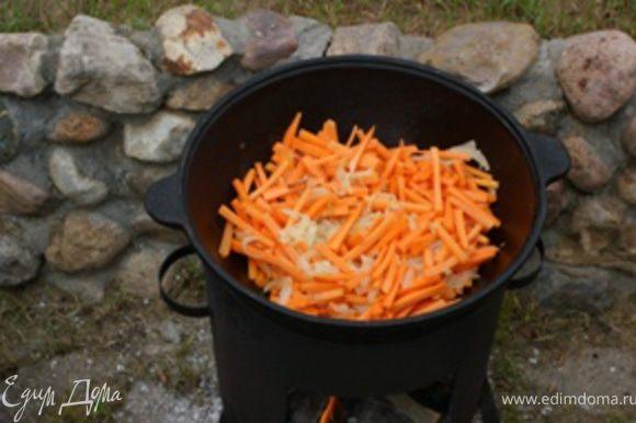 Морковь помыть, очистить и порезать брусочками (толщина около 5 мм, длина около 5 см - т.е. как для плова) и добавить к луку. Продолжать тушить 15-20 минут. Огонь средний.