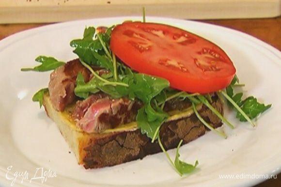 Смазать один кусок хлеба горчицей, выложить нарезанное мясо, сверху руколу и кружок помидора.