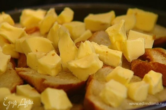 Оставшееся масло нарезать кубиками, выложить сверху на шарлотку и присыпать оставшимся сахаром, чтобы получилась карамельная корочка.