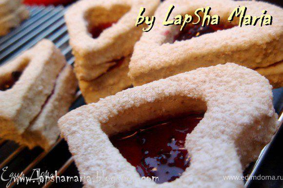 Выложить печенье на решетку и дать немного остыть. Затем на цельные сердечки тонким слоем намазать джем. Сверху плотно положить сердца с дыркой. Советую использовать густой джем или конфитюр, чтобы он не растекался и приклеивал друг к другу части печенья. Присыпать сахарной пудрой. Дать печенью 5 минут на склейку, а затем положить в образовавшуюся нишу ещё немного джема.