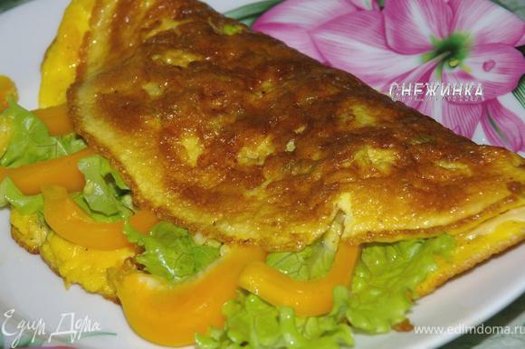 Готовый омлет сворачиваем пополам, вложив в него листья салата и перец, выкладываем на тарелку.