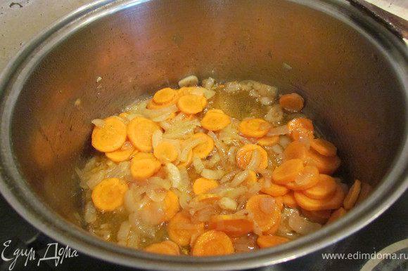 Нарезать кружками морковь и добавить к луку и чесноку, томить минут 5.