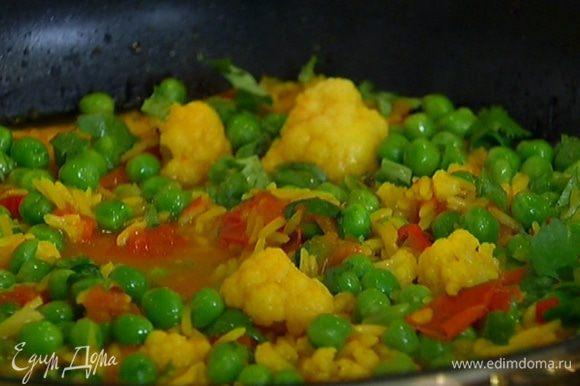 Добавить к рису зеленый горошек и кинзу, перемешать и держать на огне еще 5 минут.