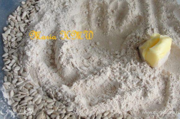 В серединку всыпаем сухие дрожжи, сахар и соль. Масло и 3 ст.л. семечек всыпаем с краю и заливаем 300 мл теплой воды.