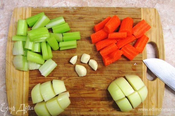 Почистите морковь и порежьте на крупные куски - по два сантиметра. Разрежьте каждый вдоль. Обрежьте концы стеблей сельдерея и порежьте также по два сантиметра. Широкие куски - вдоль пополам. Очистите лук и порежьте крупно на 8-12 частей (у меня получилось сначала пополам, потом еще раз пополам, потом каждую четвертинку на три части). Овощи не надо резать мелко. Иначе потом вам трудно будет разделить капусту и остальные овощи. Немного раздавите зубчики чеснока так, чтобы кожица лопнула. Теперь отрежьте попки и снимите кожицу. Она очень легко слезет.