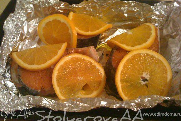 Апельсин вымыть и нарезать кружками вместе с кожурой. Семгу посыпать орегано, тимьяном, посолить, поперчить и выложить в жаропрочную форму. Взбрызнуть рыбу оливковым маслом, обложить кружками апельсина и оставить мариноваться на 20-30 минут.